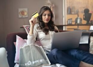 teen girl holding a credit card looking at a laptop